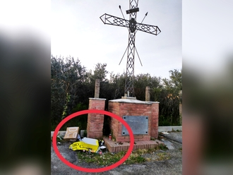 Mangiano e lasciano i cartoni sotto la Croce davanti al Cimitero